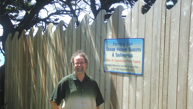 Jeffery installs a new sign on the fence he designed for Ocean Haven.